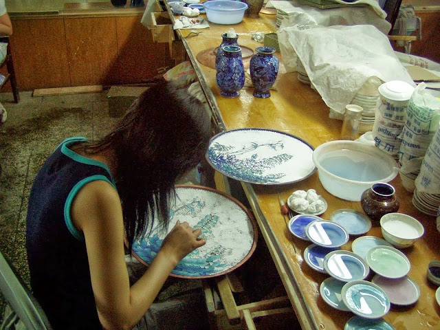 Crafts in Beijing working on a plate