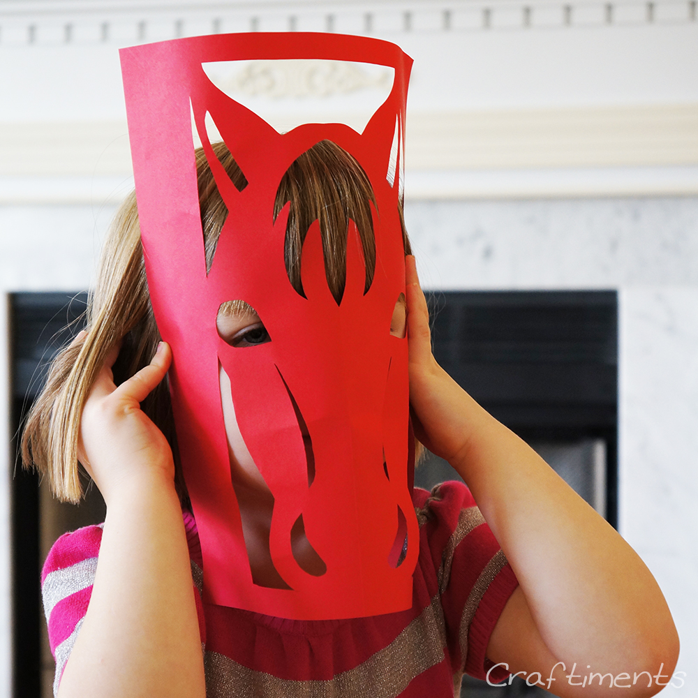 child using horse paper cutting as a mask