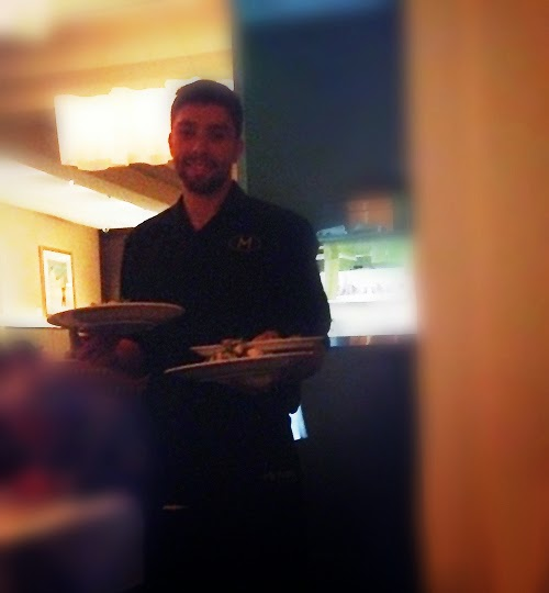 bearded waiter carrying plates balanced on his arms