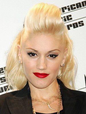 With smoothed-tight sides, Gwen Stefani rolls back the top of her curly locks for a volumized pouf in front.