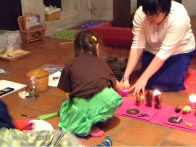 This is a rather jumbled picture - there are several baskets visible on the left, as well as a spray bottle of cleaner and a crumpled paper towel, and some papers and crayons. The focus of the picture, however, is of the Storyteller in the back right of the photo, kneeling, and holding the edges of a candle holder, and a young girl in the center of the photo who is down on one knee and leaning forward to snuff out the candle with a small snuffer.