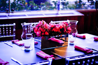 mesa preta, cadeiras transparentes, vaso espelhado, arranjo floral rosa