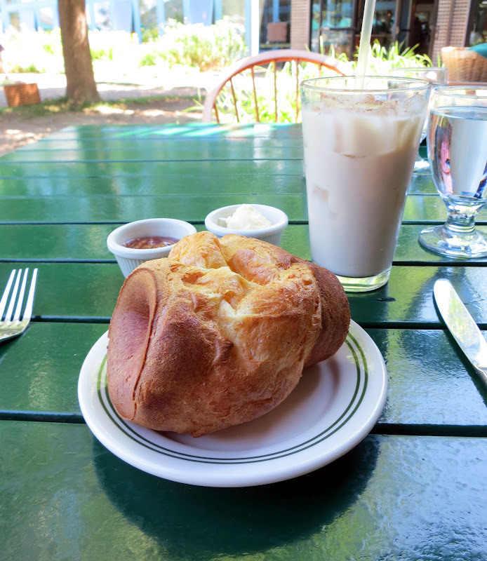 hot popover awaits its butter and jam, accompanied by iced chai.