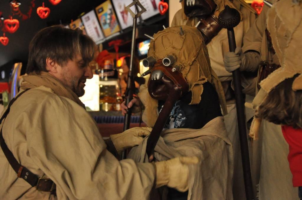 Stary Tusken pomaga mlodemu ubrac sie w pustynny stroj