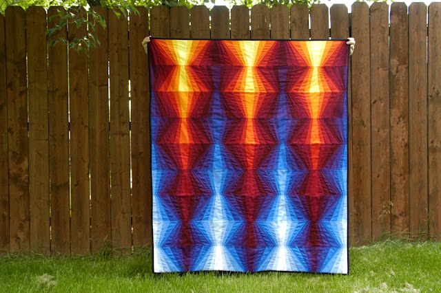 Bright Red and Blue Quilt Hanging Against Fence