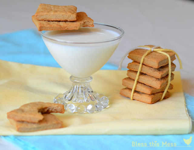 Graham Crackers sitting next to a glass of milk on a yellow cloth.