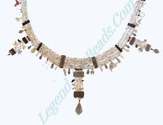 This necklace consists of ten rows of beads with amulets representing objects in everyday life.