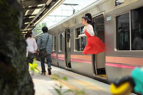 Fotografia de uma garota saindo do vagão de metrô. Ela está de saia e suas pernas não aparecem, como se estivesse levitando ao sair do vagão.