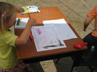 Asztalon heverő Törpmanós papírok, amik olyan formán vannak összefirkálva, ahogyan egy 2-3 éves gyermek tudja produkálni.