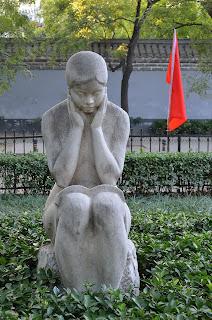 Sculpture of girl reading a book in park on Zheng Yi Lu in Beijing