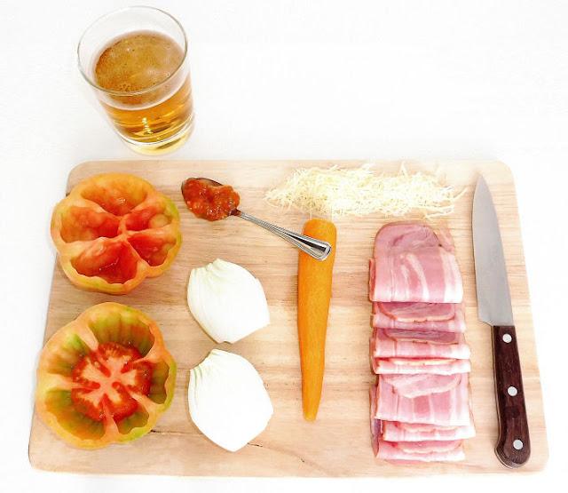 Ingredientes para realizar tomates rellenos de bacon a la cerveza sobre una tabla de madera