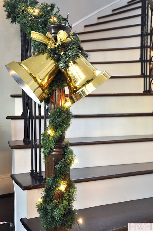 Festive holiday garland wrapped around the staircase with large gold bells - Merry Christmas! | Honey We're Home