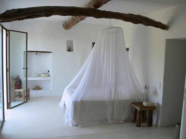 cama con mosquitera blanca en dormitorio