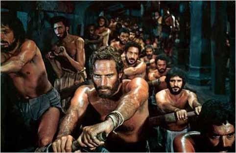 """Cette image est extraite du film """"Ben-hur"""" réalisé par William Wyler en 1959 et adapté du livre éponyme de Lewis Wallace paru en 1880. ce péplum épique dont l'action se situe au début de notre ère est un monument de l'histoire du cinéma par l'ampleur de sa mise en scène et des séquences à très grand spectacle comme la bataille navale , la course de char, et la crucifixion. Il demeure également l'un des films les plus primés avec onze Oscars. L'image choisie montre Ben-Hur, interprété par Charlton Heston, en train de ramer aux galères : il apparît au premier plan de l'image et d'une colonne de co-détenus qui comme lui rament, avec pour tout habit une espèce de pagne en tissu recouvrant les parties intimes. On peut lire de la détermination dans le regard de Ben-Hur. Cette image illustre le poème """"Le même bateau"""" du Marginal Magnifique dans lequel le poète explique que tous les hommes sont dans meme bateau, ce qui est une métaphore pour signifier que la vie est finalement la même pour tous, que nous sommes tous égaux, mais que nous n'avons pas les mêmes chances au départ, ce qu'il ne faut pas oublier afin de ne pas juger les autres. Dans ce poème, Le Marginal Magnifique mentionne aussi le personnage de fiction Gatsby qui apparaît dans le livre de Francis Scott Fitzgerald, également adapté au cinéma en 1974 par Jack Clayton, avec dans le rôle titre Robert Redford."""