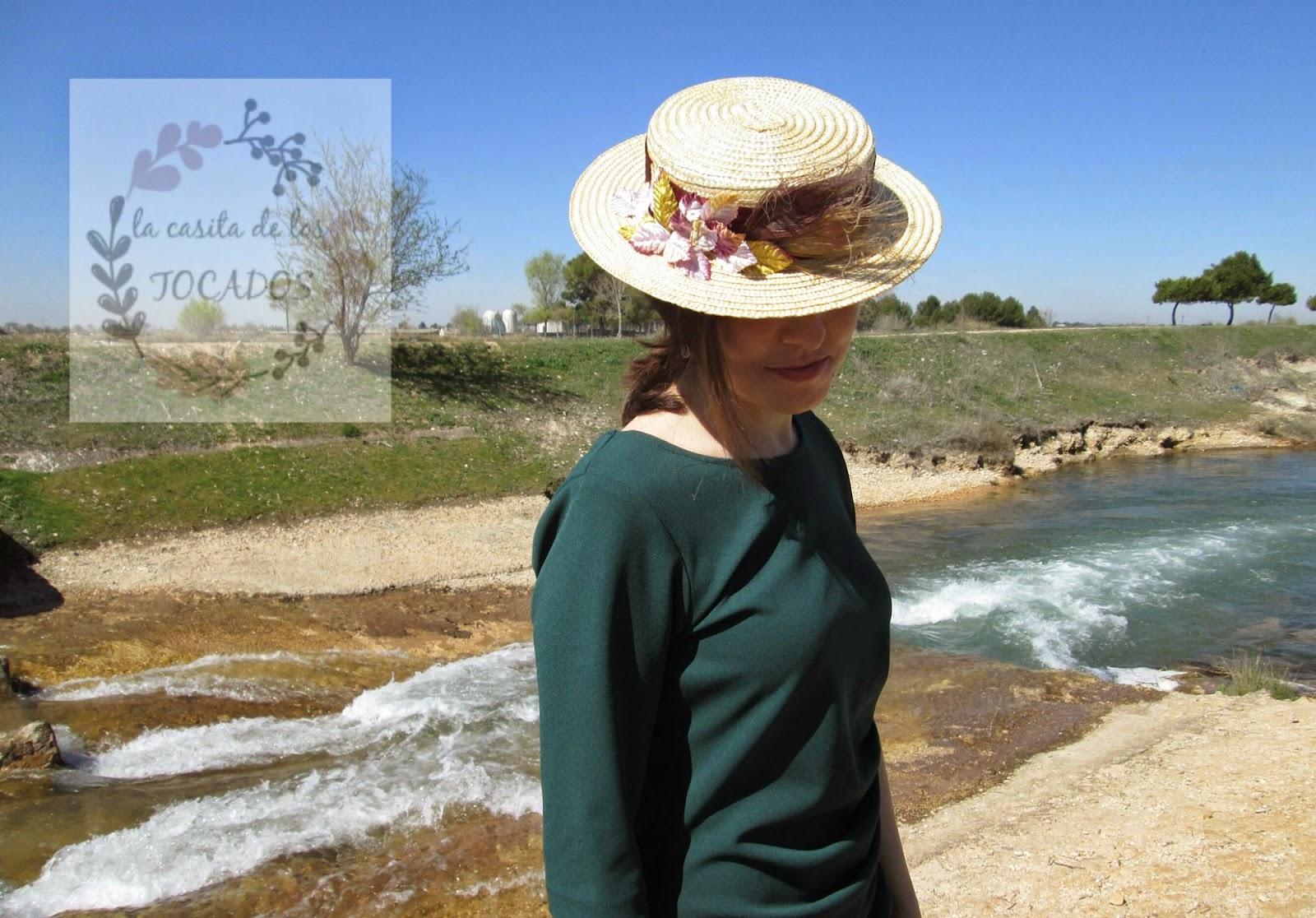Canotier Melíade con plumas y hojas en dorado, lavanda y morado, combinado con vestido en color verde.