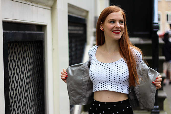 Vintage fashion blogger outfit with a polka dot crop top and a grey faux leather jacket