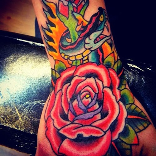 Tattoo of a colorful rose with flaming snake by Tattoo artist Mark Stewart for Triumph Tattoo
