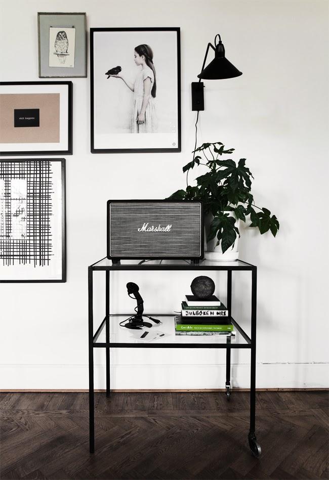 indretning med grønne planter og kunst på væggen