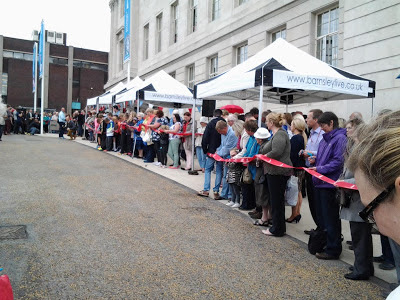 People lined up down the side of the Town Hall under the gazebos holding the ribbon with their blue scissors poised