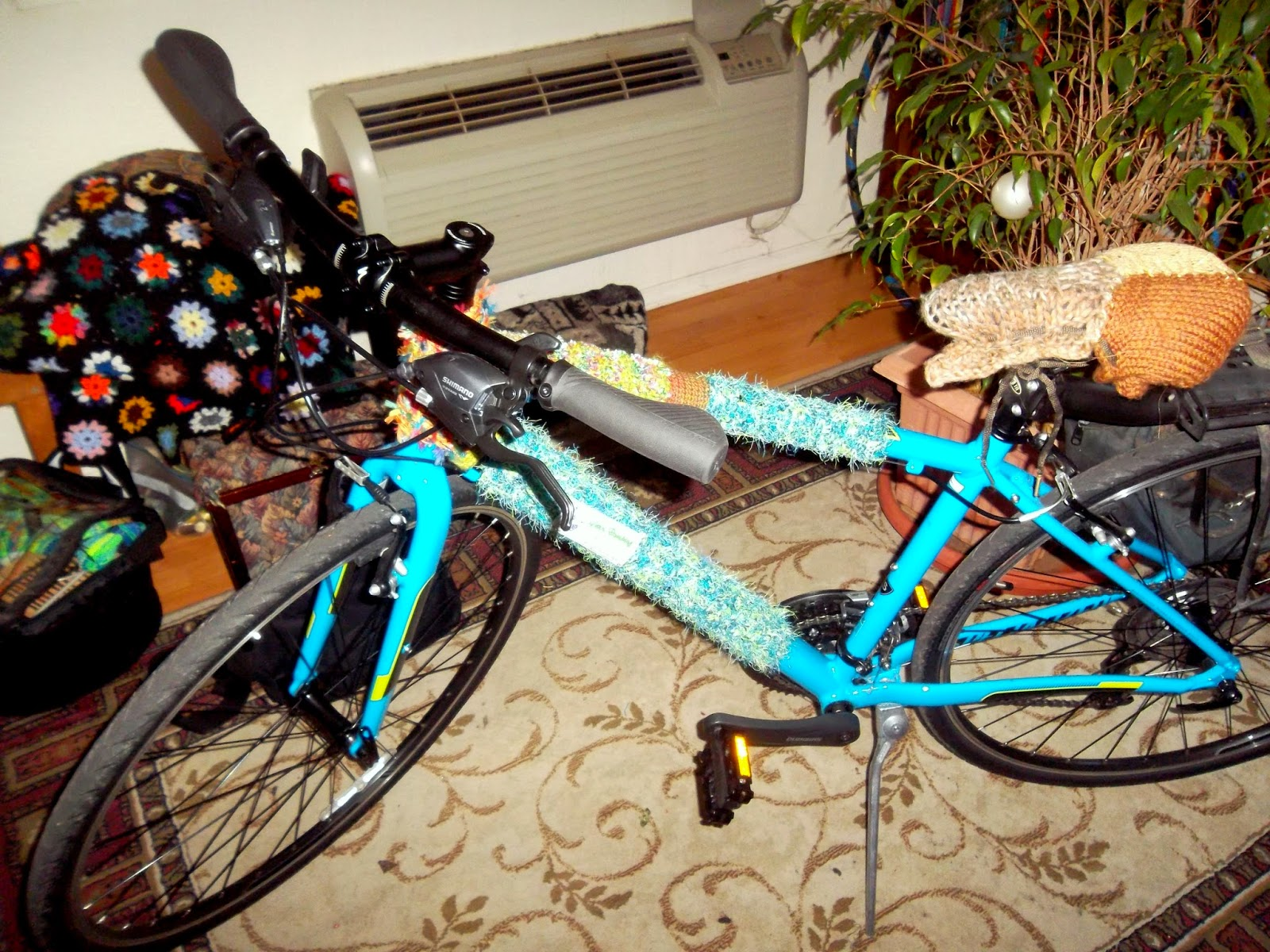 Bright teal-blue, diamond framed bicycle, with yarn bombing tags around the top tube, head tube and down tube of the frame. Knit swatches assembled into a seat-cover are tied over the bicycle seat.