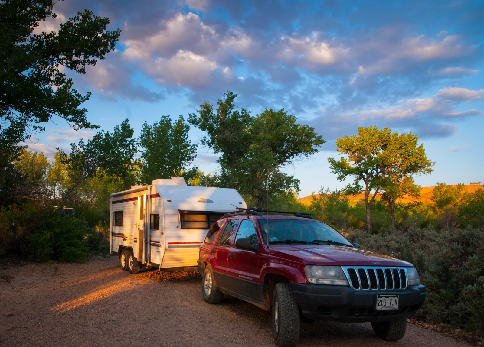 Sunrise from a tree filled campsite, a photo of my tow vehicle and an 18 foot travel trailer