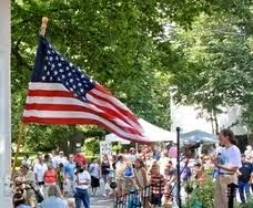 American flag waving over people at the street fair