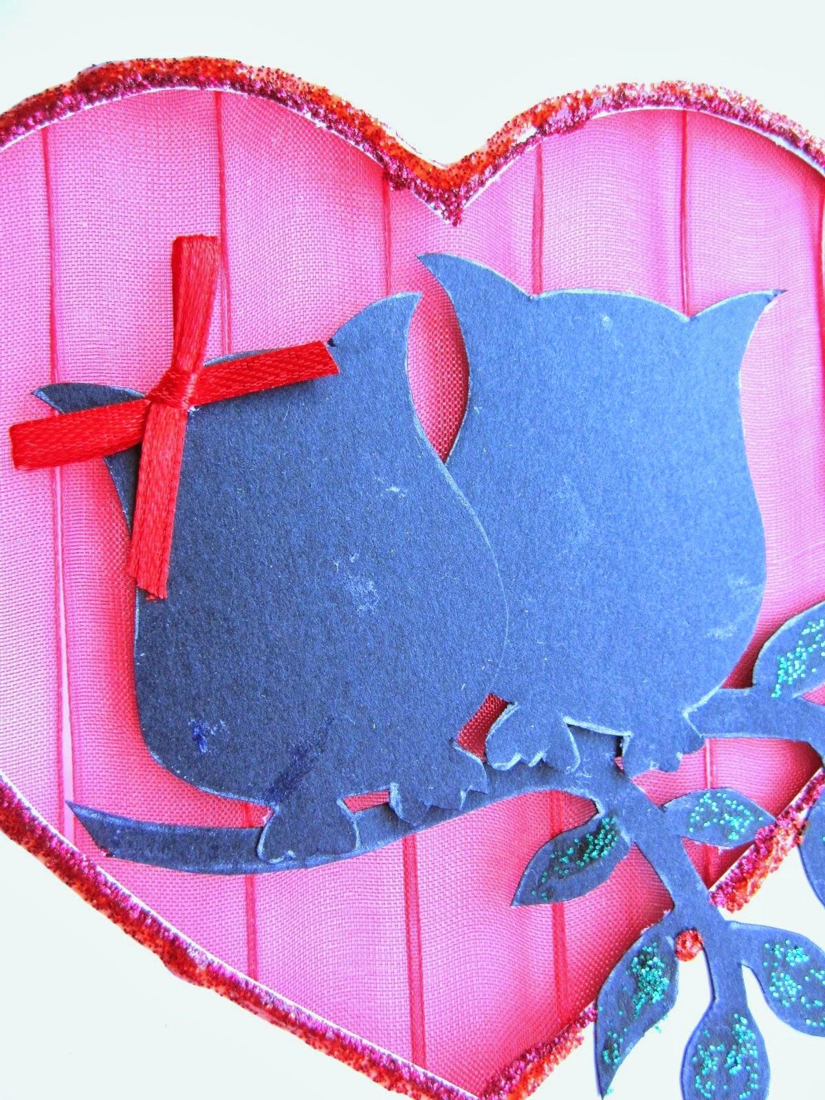 detalle de tarjeta blanca de felicitación con corazón calado con fondo de gasa roja y siluetas delante de dos búhos y rama de árbol con detalles decorados con glitter glue rojo y verde