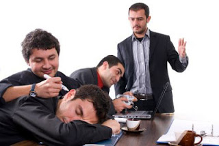 Photo image of a business meeting where the executives seem much more interested in playing video games or playing pranks on sleeping coworkers.