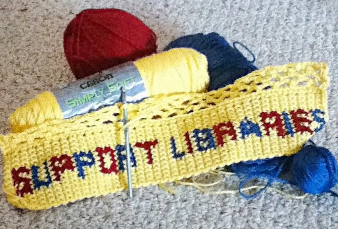"Crocheted rectangular panel reading ""Support Libraries"" lengthwise, with several rows of crocheted mesh in progress along the top long edge. The piece is worked in yellow and the letters are in alternating burgundy and blue."