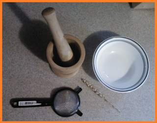 wooden mortar and pestle, small bowl, 1 stem with grains attached, a sieve (actually a tea strainer)