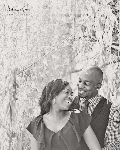 engaged couple underneath a willow tree in black and white