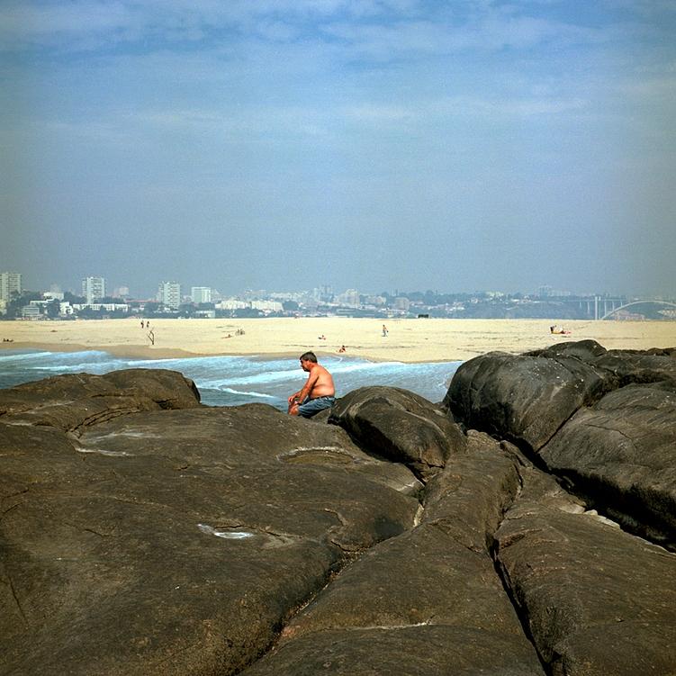 Apontamento nas rochas junto ao mar, onde uma pessoa comtempla o lugar e a paisagem. Ao fundo a cidade do Porto. Céu limpo.