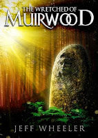 cover of The Wretched of Muirwood by Jeff Wheeler shows a bolder with a face carved onto it sitting in a clearing in the woods