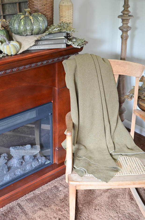 A green army blanket adds a cozy touch when tossed on a rocking chair.