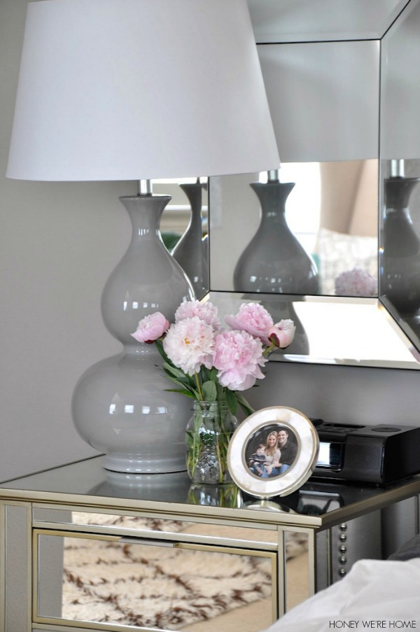 neutral master bedroom, mirrored nightstand and gray lamp