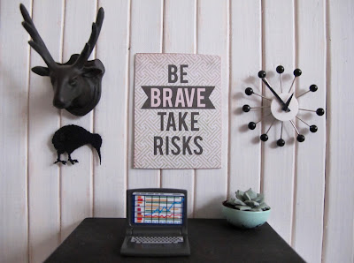 A modern dolls' house miniature desk scene in white, black and mint. On the wall above the desk is a plastic stag's head, a kiwi cutout, an atomic-age clock and a poster saying 'Be brave take risks.'
