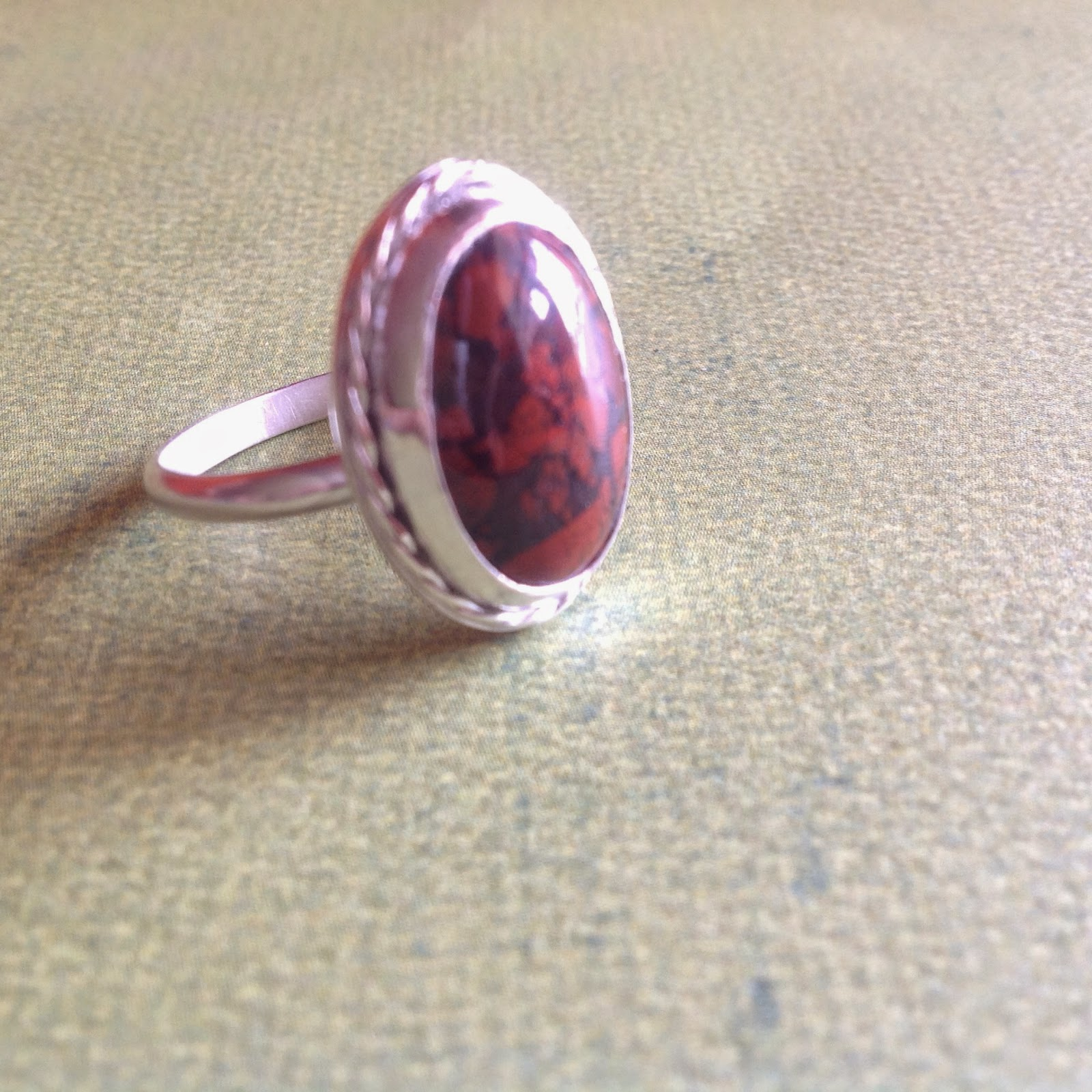 Red cabochon ring with twisted silver wire around it