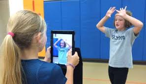 A girl videoing another learning how to set a volleyball