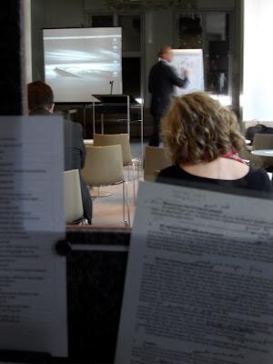 Blick aus der Kabine auf Redner und die Rücken von Zuhörenden