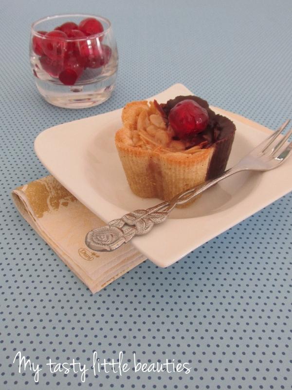 Ein Törtchen auf einem Teller, ein Glas mit Kirschen im Hintergrund