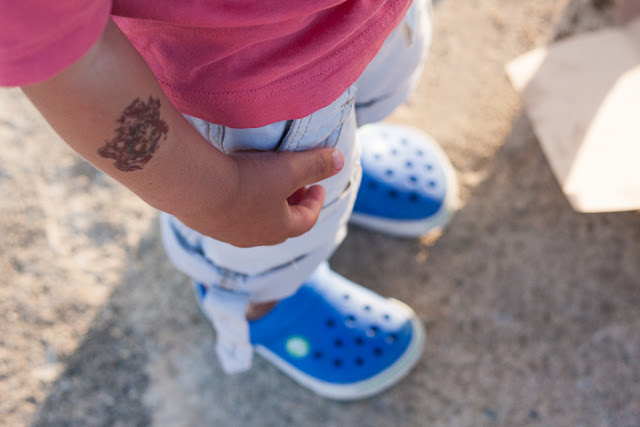 view from above of little boy's tattooed arm and blue crocs