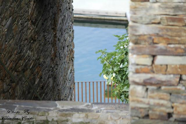 Uma fotografia com desfoque e vários planos de imagem. Entre paredes de xisto e por onde aparece uma pequena arvore que nos leva até ao rio.