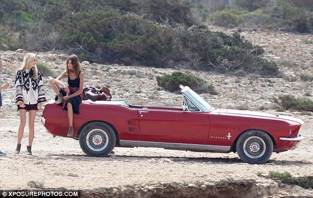 Na imagem: uma carro conversível vermelho parado numa estrada de terra. Na caçamba tem uma garota sentada com um pé pra cima e a mão apoiada no joelho, enquanto outra garota está em pé ao lado
