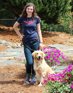 Laura Marchi poses with a Golden Retriever with purple flowers around them.
