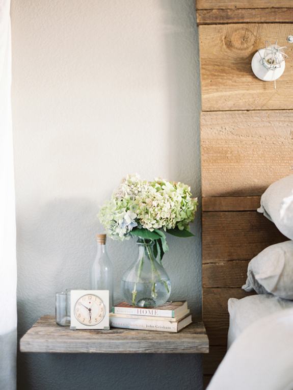 simple beside table with hydrangeas, books, and classic clock