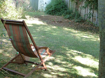 Deck chair on my lawn in dappled sunlight