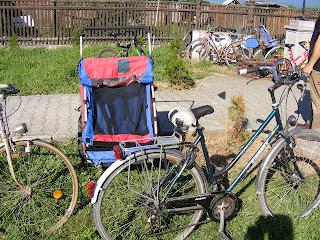 Biciklik rendezett összevisszaságban. Közelkép egy piskótakővel kirakott járórészről, ami körül a gyepen kisebb-nagyobb, különböző típusú bicikli van felállítva.  Előtérben Törpanyu biciklije az utánfutóval. A bicikli ülése, valamitn a bal kormányfogó papírragasztóval van lekötve.
