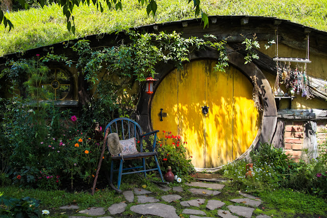 a hobbit hole with a bright yellow door