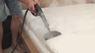 Man steam cleans a mattress