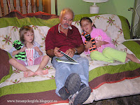 Grandfather reading to two grandchildren